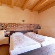 Schlafzimmer mit Dekosteinwand, Holzdekce, bezogenen Betten auf einen dunkelbrauen Bett