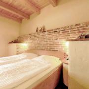 Schlafzimmer mit Holzdecke, Gardinen am Fenster und bezogenen Betten, sowie Nachtischlicht.