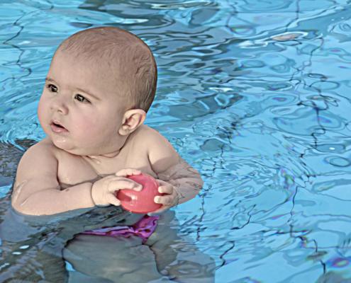 Baby im Schwimmbad mit Ball in der Hand