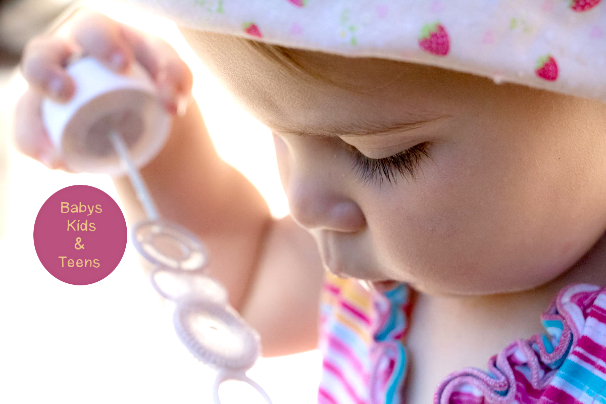 Ein Baby mit Hut und sommerlicher Kleidung bläst in eine Seifenblase