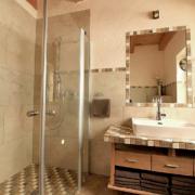 Badezimmer mit begehbarer Dusche, einem Waschbecken und umrahmten Spiegel