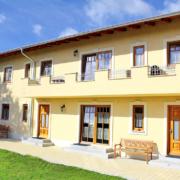 Haus mit gelblicher Farbe, Rasen vor dem Haus und der Himmel ist strahlend blau