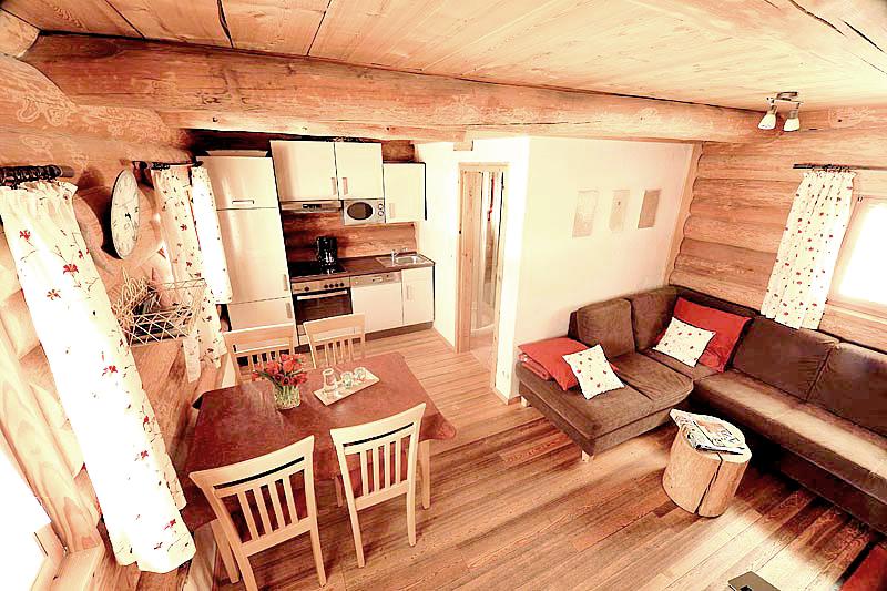 Blockhuette-Naturstammhaus mit Holzboden, Couch, Essecke und Küche, sowie Badezimmerbereich