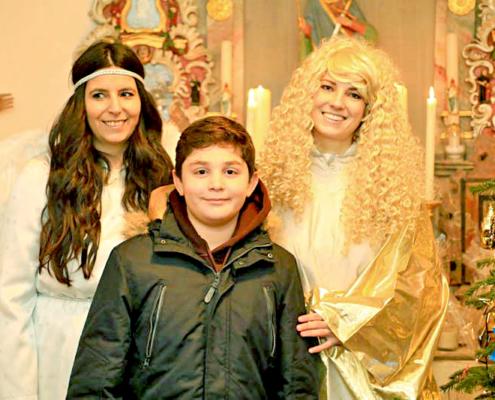 Christkind in der Kapelle mit Engel und einem Jungen in der Mitte, daneben ist ein Christbaumen