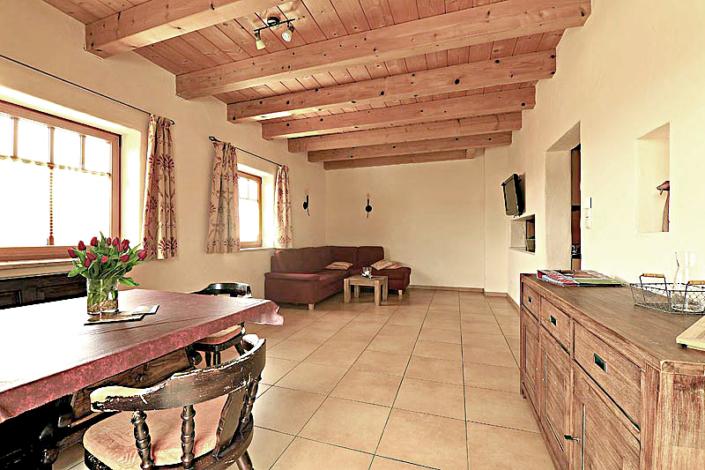 Wohnbereich mit Holzdecke, Essecke und Couch mit Durchreiche zur Kueche