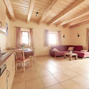 Sonnige Ferienwohnung mit Couch und Couchtisch, Fliesenboden und Holzdecke, sowie eine Küche