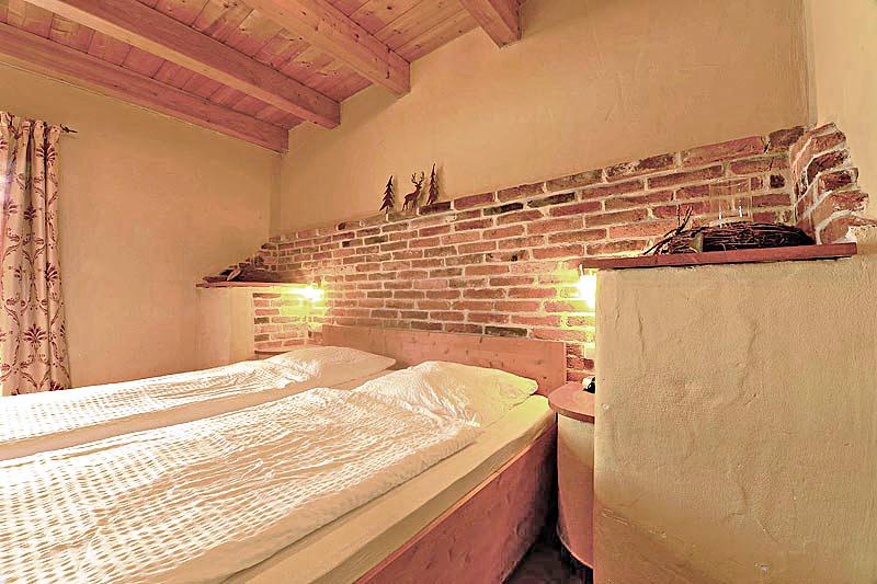 Schlafzimmer mit Bett, Bettwäsche. Eine Holzdecke und Natursteine an der Wand