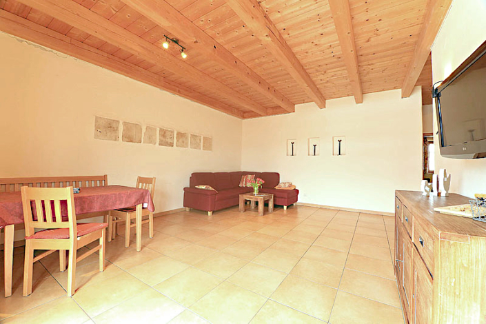 Ferienwohnung mit Holzdecke, Essecke und einer Couch, sowie SAT/TV und Sideboard