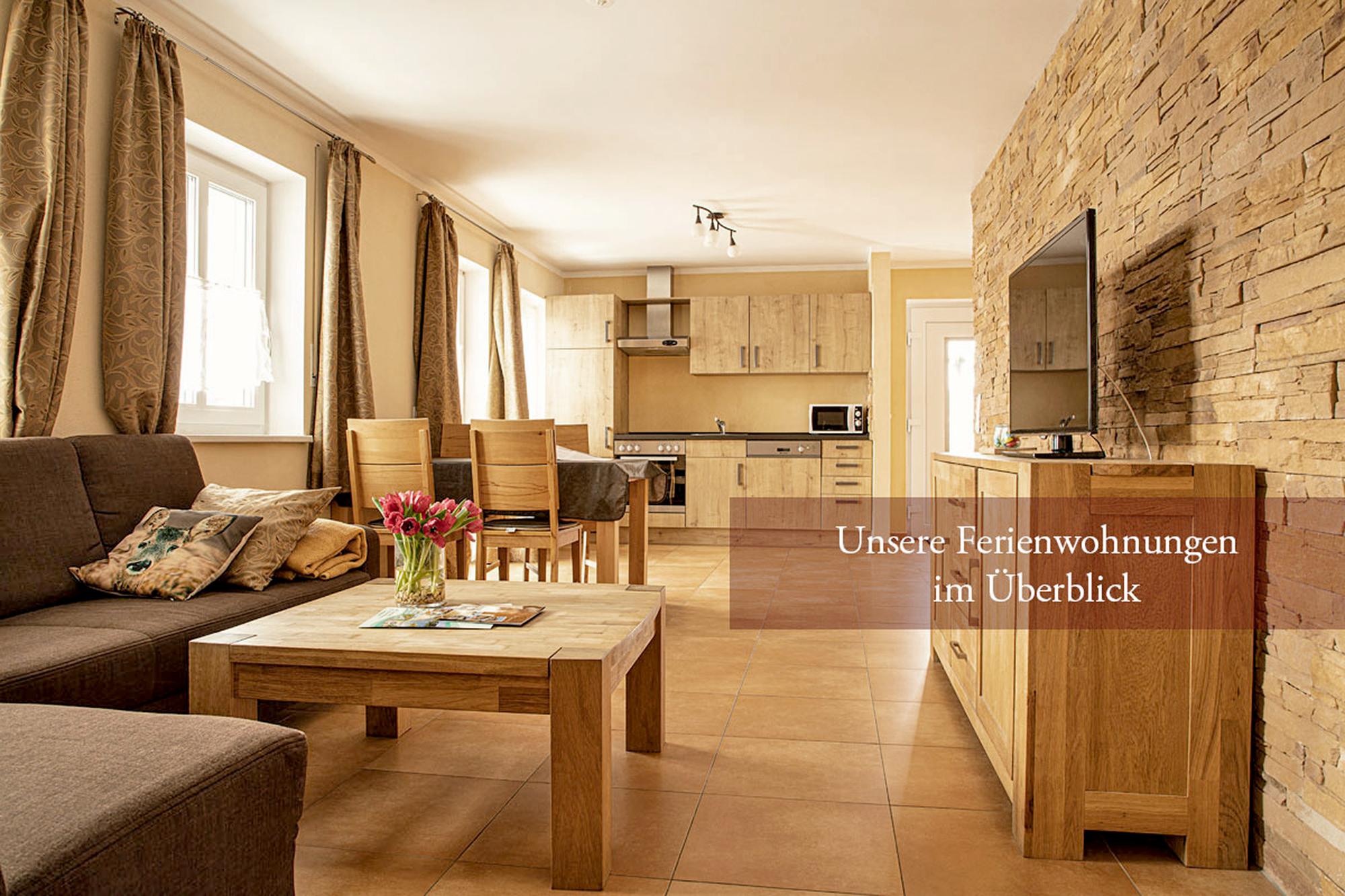 Ferienwohnung mit Couch, tisch, Essecke und Sideboard, sowie eine ausgestattete Kueche, TV und Fenster mit Gardinen
