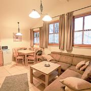 Ferienwohnung mit Couch und Essecke, sowie Kueche, drei Fenster mit Gardinen