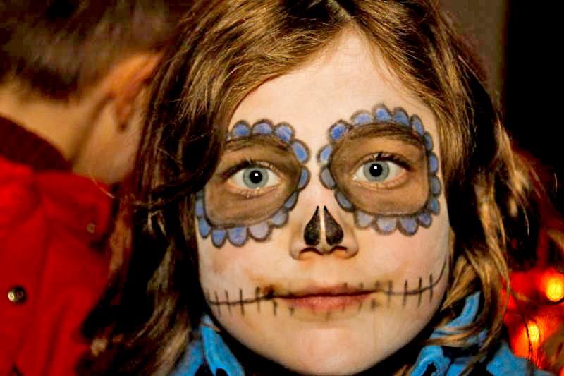 Geschmincktes Kind zu Halloween mit blauen Ringeln um die Augen