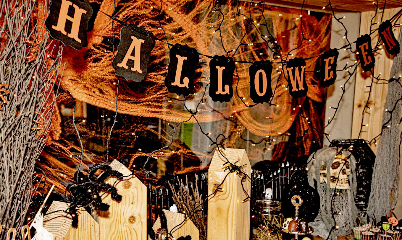 Halloweenparty mit Decoration aus Spinnen, Reisig, Holztürmen und mit einem Bufett