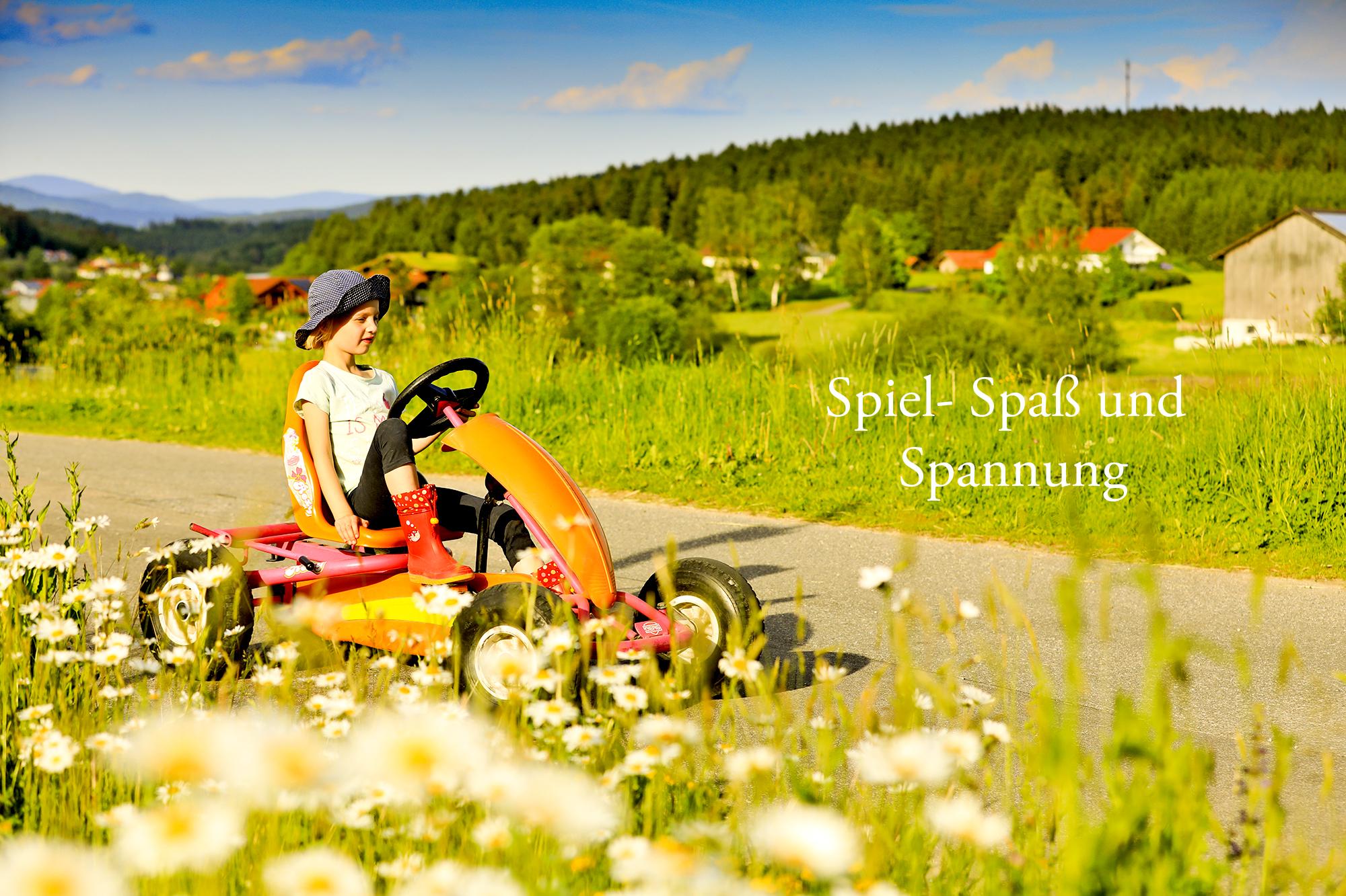 Ein Mädchen fährt auf der Straße mit dem Kettcar in einer schönen Landschaft