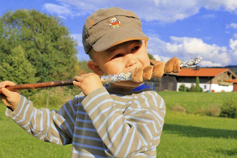 Ein Kind ist vom Stockbrot auf der Wiese bei weißblauen Himmel