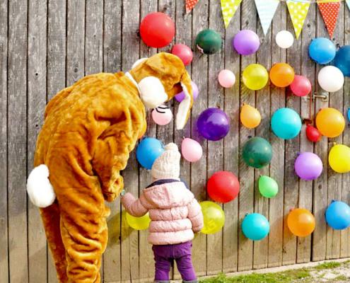 Lebensgroßer Osterhase mit Kind in rosa Jacke und Mütze,sowie viele bunte Luftballons an der Holzwand