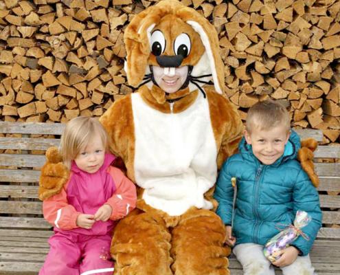Großer Osterhase umarmt zwei Kinder, dahinter ist eine Holzschar