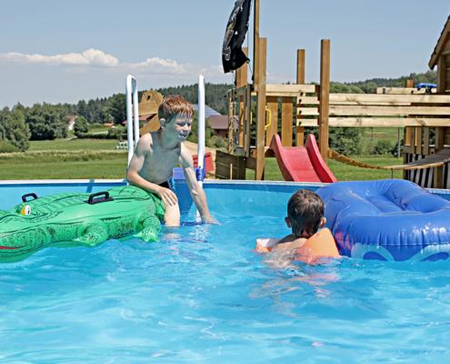 Zwei Kinder spielen auf der Luftmatraze im Pool von Paulas Bauernhof