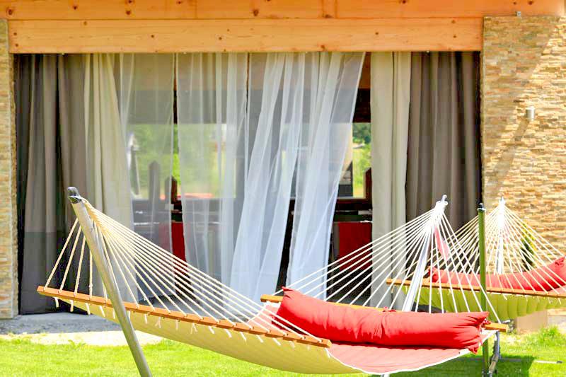 Rote Hängematten auf der Liegewiese, am Freisitz hängen Vorhänge