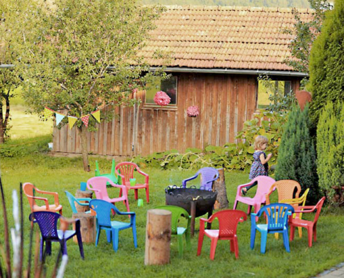 Lagerfeuerplatz mit vielen bunten Stühlen in der Wiese