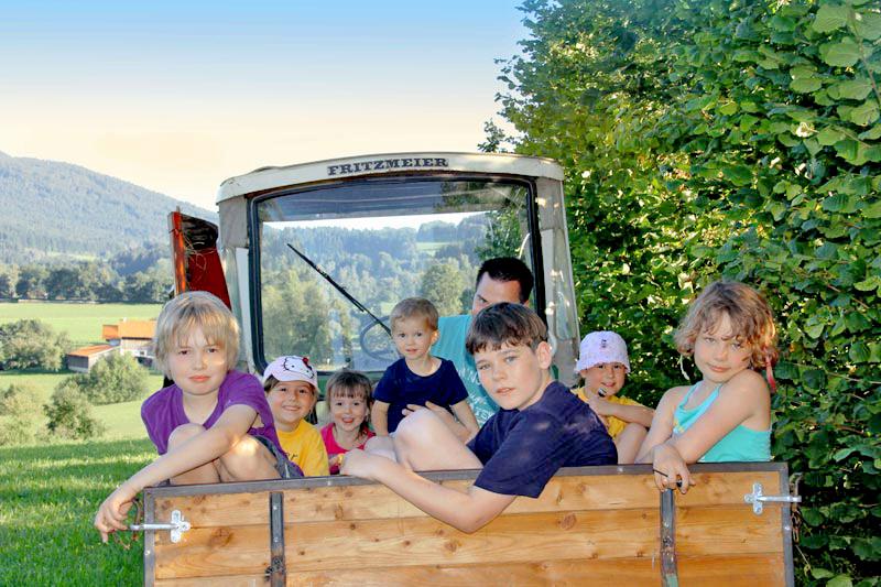 Viele Kinder auf dem Traktorauf einer Wiese