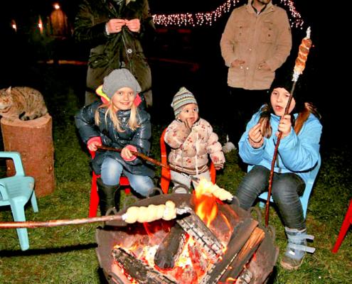 Kinder am lodernden Feuer mit Stockbrot und Würsetl