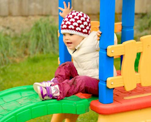 Kind mit Mütze auf einer bunten Babyrutsche