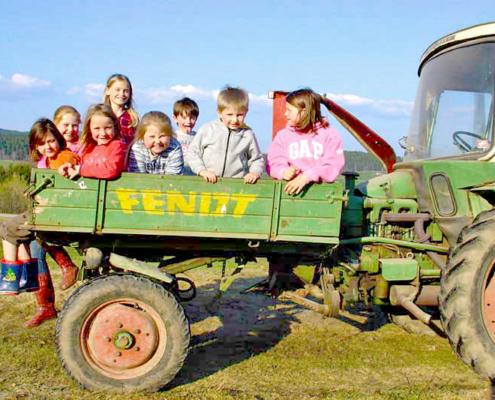 Acht Kinder sitzen auf einen Fendt Geräteträger auf einer Weise