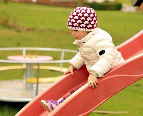 Kind auf einer roten Rutsche im Hintergrund ein Karusell