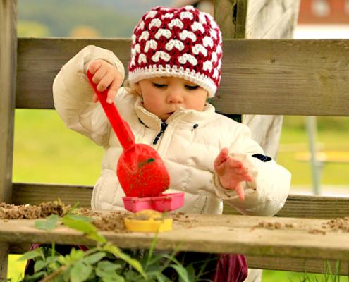 Ein Kind mit roter Mütze spiel mit dem Spielsand.