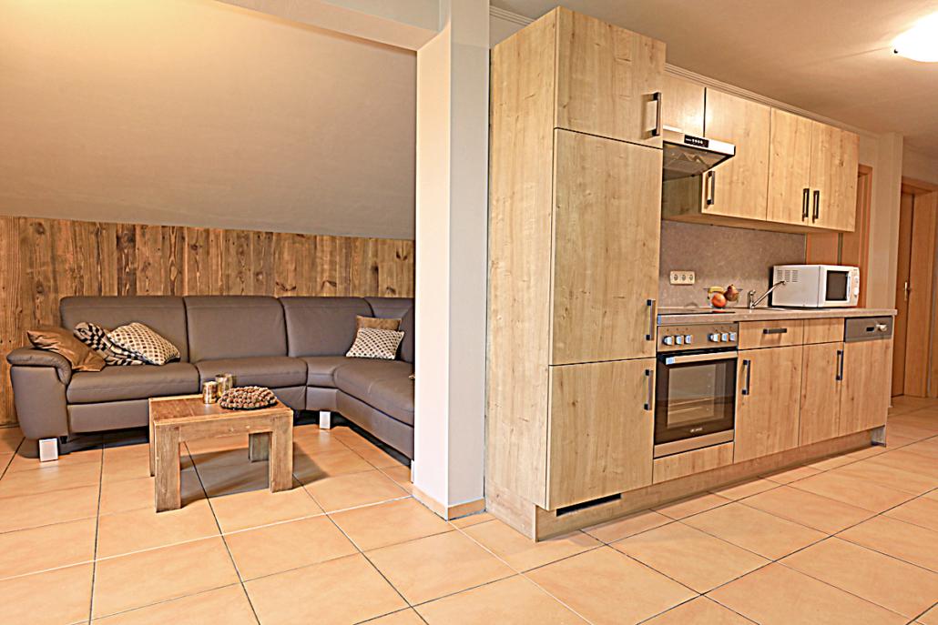 Ferienwohnung mit einer Holzwandbekleidung und einer Holstrukturkueche, sowie Couch und Couchtisch