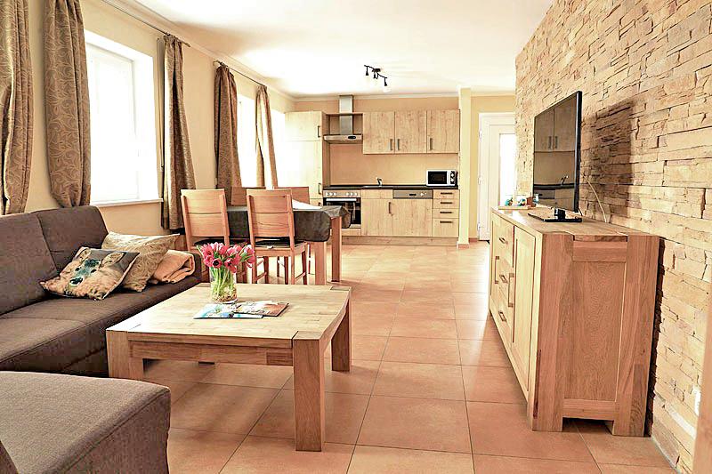 Ferienwohnung mit brauner Couch einer Essecke, sowie ein Sideboard mit TV