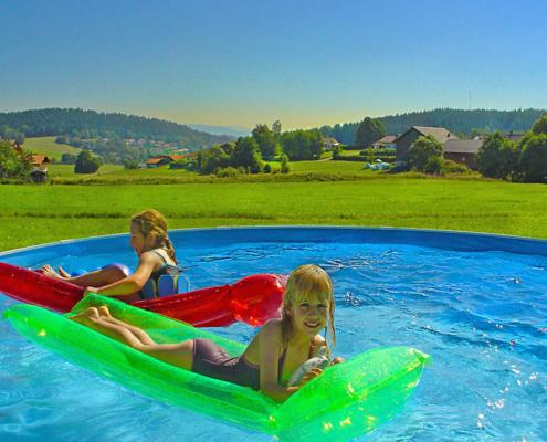 Inmitten schöner Landschaft spielen zwei Kinder auf der Luftmatraze im Pool