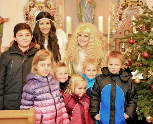 Christkind und Engel mit Kindern in einer Kapelle mit Weihnachtsbaum