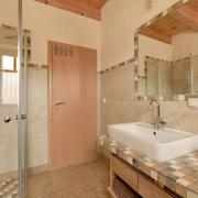 Badezimmer mit begehbarer Dusche, Waschbecken und Wandspiegel