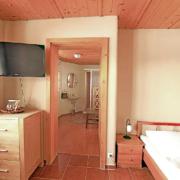 Apartment mit Bett, TV, Sideboard und Türe zum Badezimmer