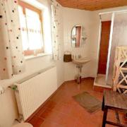 Badezimmer mit Dusche und WC, ein Heizkörper, Stuhl und Regal, sowie ein Waschbecken