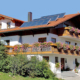 Ferienhaus mit großen Balkon, darauf viele Geranien und Sträucher um das Haus