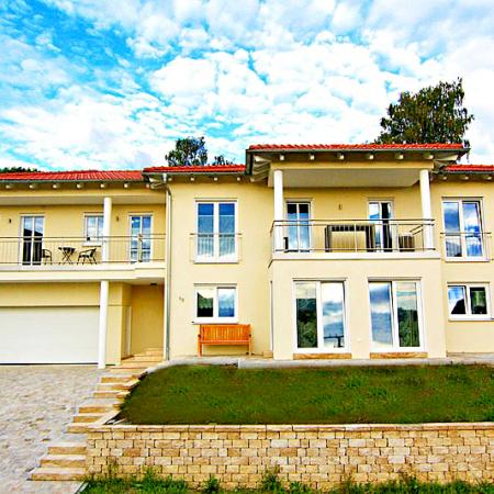 Toskana Haus mit blau weißen Himmel und Rasenfläche vor dem Haus
