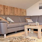 Wohnbereich mit Holzwand, einen Tisch, Couch mit Polster und Dece, sowie ein Fell auf dem Boden