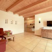 Große Wohnung mit SAT/TV auf Sideboard und Küche mit Couch und Couchtisch, sowie einer Holzdekce