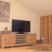 Wohnung mit großem Bild an der Wand, ein Fell am Boden, einer Dekoholzwand und ein Fell auf dem Boden