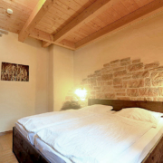Schlafzimmer mit Holzdecke, brauen Holzbett und bezogenen Betten, dazu Wandleuchten und ein Foto an der Wand
