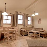 Ferienwohnung mit drei Fenster, Couch und Essecke, sowie Küche,Teppich, und eine Tür