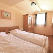 Schlafzimmer mit Fenster, Kleiderschrank, Babybett und Einzelbett, bezogene Bettwäsche und einem Bild an der Wand