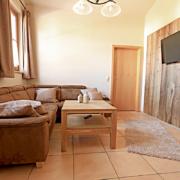 Ferienwohnung mit Couch,SAT/TV, einen Teppich und Fenster, sowie einen Lampenschirm und Wanddeko aus Holz