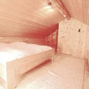 Schlafzimmer im Dachgeschoß mit vier großen Betten einem Regal und einer Tür, sowie Licht