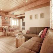 Wohnbereich in einem Chalet mit einem Rundstammtisch und Steinplatten an der Wand, sowie eine Essecke und eine Küche