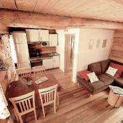 Ein Naturstammchalet eingerichtet mit Couch, Essecke, Küche und Badezimmer