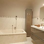 Badezimmer mit Badewanne Duschkabine und Badmöbel, Waschbecken mit Spiegel und Handtücher