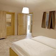 Schlafzimmer mit Bett und Bettwäsche, Fenster, Türen und Kleiderschrank